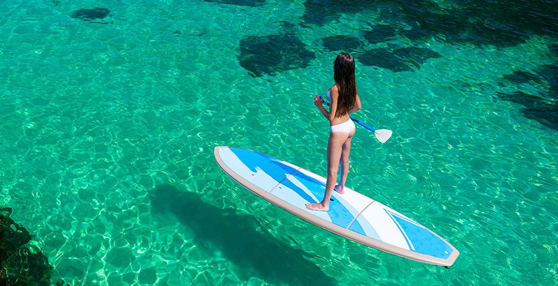 Young attractive woman in the sea on the Stand Up Paddle Board